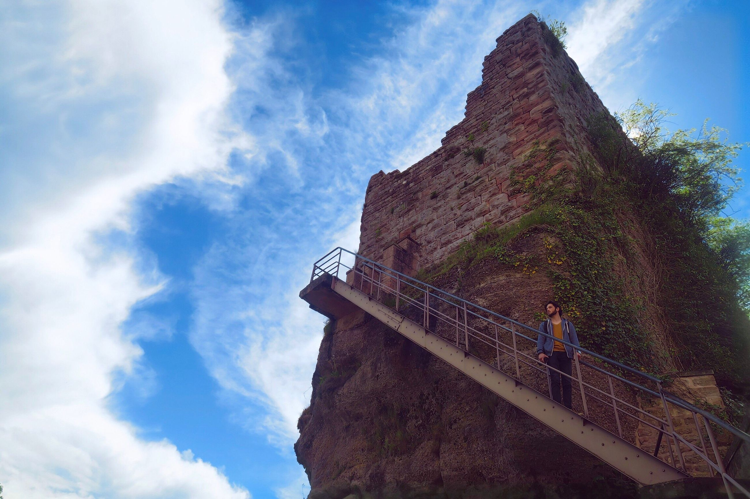 sky, low angle view, cloud - sky, real people, architecture, day, outdoors, rock - object, men, climbing, built structure, leisure activity, mountain, nature, lifestyles, women, one person, scenics, adventure, beauty in nature, building exterior, young adult, people