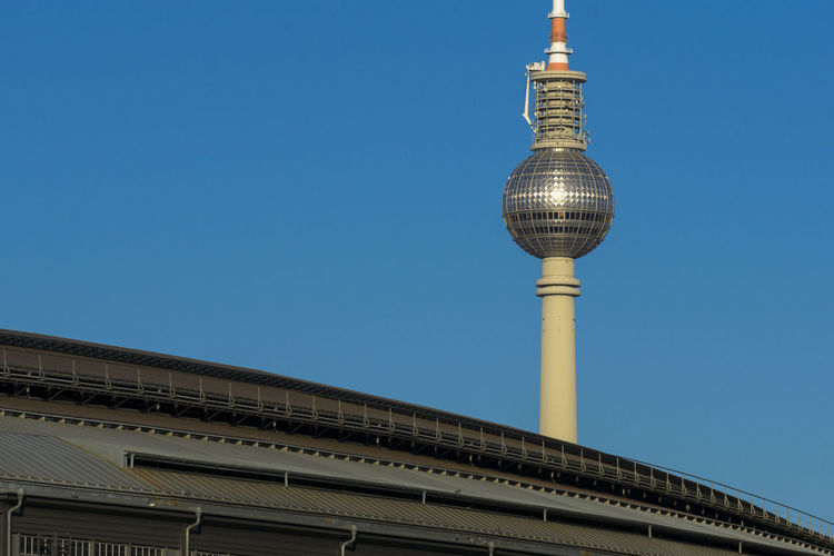 Low angle view of fernsehturm tv tower against blue sky