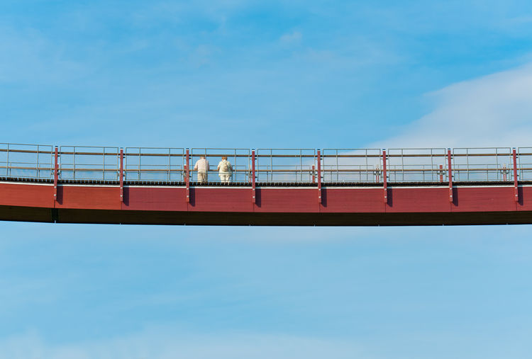 unrecognizable persons on a high above hanging bridge Sky Low Angle View Architecture Nature Blue Day Built Structure Railing Connection Cloud - Sky Bridge Bridge - Man Made Structure Outdoors Copy Space Building Exterior Travel Symbolism Hanging Unrecognizable Person Clouds And Sky High Angle View Way High