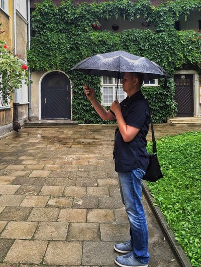 Man holding umbrella while using mobile phone on footpath against house