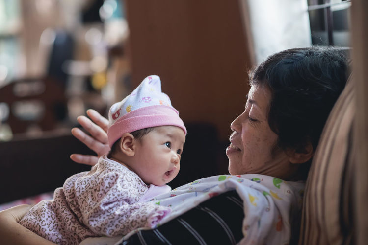 Grandmother with cute baby at home