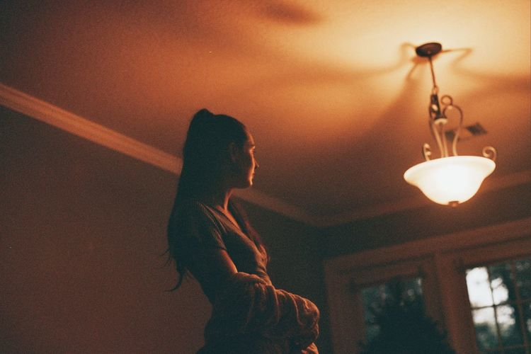 Low angle view of woman standing on illuminated ceiling