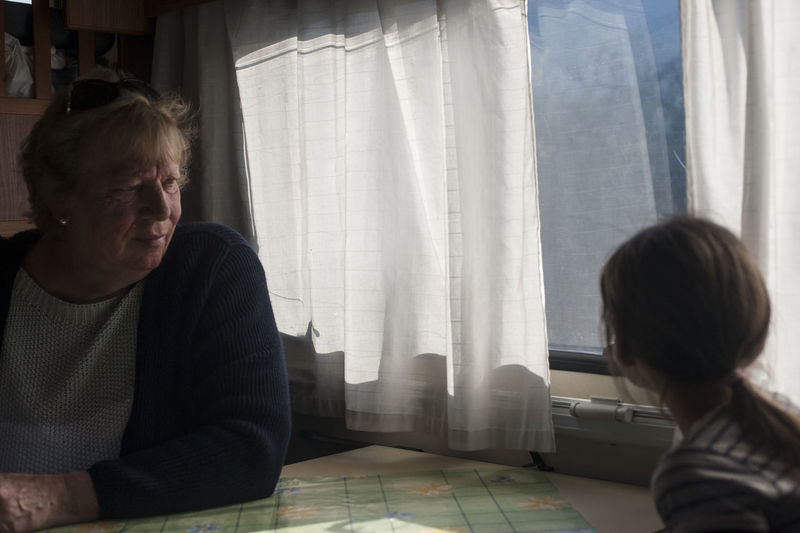 Side view of grandmother and daughter sitting by window in motor home