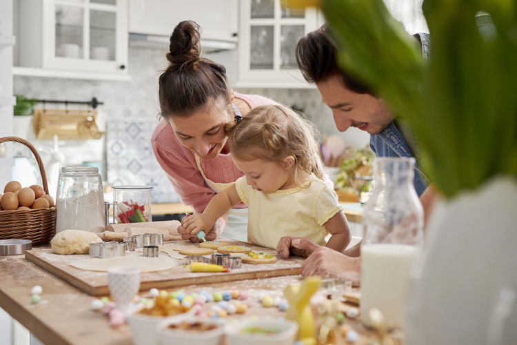 Father by mother and daughter preparing food in kitchen