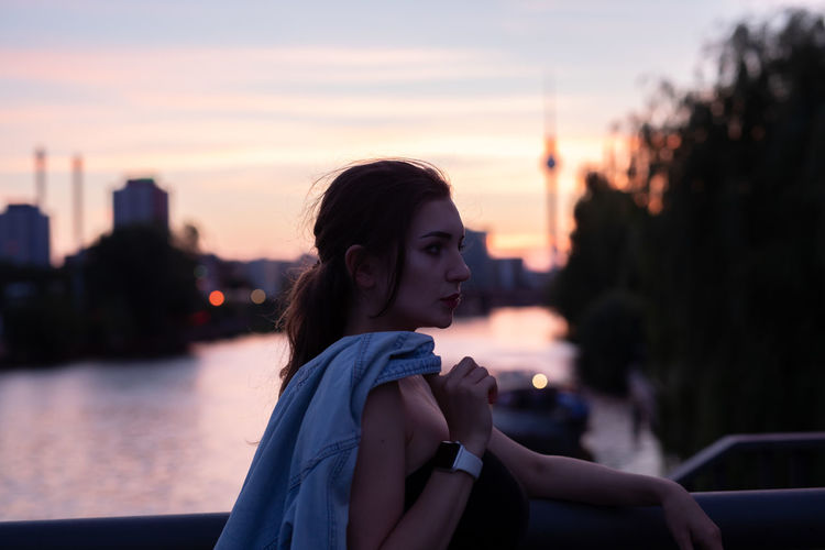 Young woman looking away while standing by railing during sunset