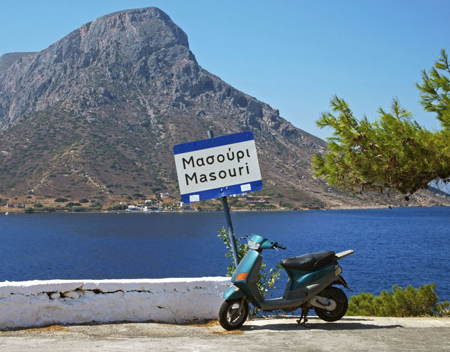 Motorcycle on road by sea and information sign against clear sky