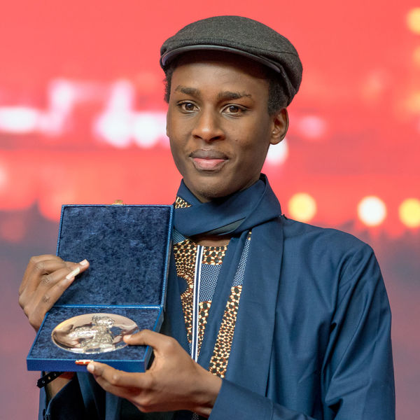 Berlin, Germany - February 24, 2018: Samuel Ishimwe, winner of the Silver Bear Jury Prize (Short Film) for the movie 'Imfura', poses at the Award Winners press conference during the 68th Berlinale AWARD Closing Ceremony Film Festival Arts Culture And Entertainment Berlinale Berlinale 2018 Berlinale Festival Berlinale2018 Close-up Entertainment Entertainment Event Front View Holding Imfura Mass Media One Person Portrait Prize Samuel Ishimwe Standing Waist Up Winner Young Adult