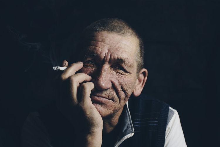 Close-up portrait of man smoking cigarette against black background