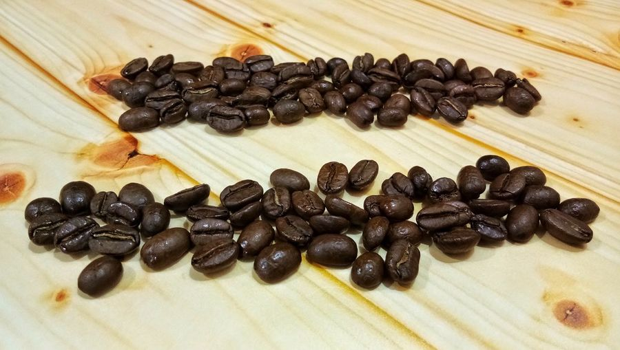 Coffee beans on wood pattern background White Background Studio Shot Black Color Table High Angle View Still Life Close-up Food And Drink Dried Food Ingredient Roasted Coffee Bean Raw Coffee Bean Coffee Bean Coffee Crop Ground Coffee Hazelnut Dark Chocolate Deforestation