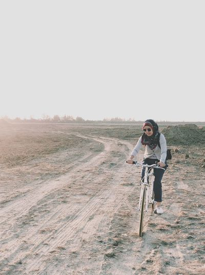 Full length of woman riding bicycle on land against clear sky during sunset