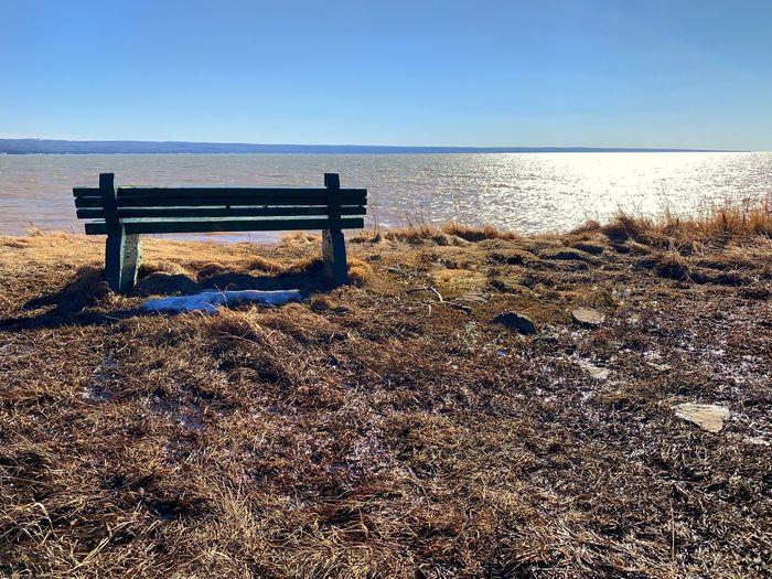 Bench on beach against clear sky
