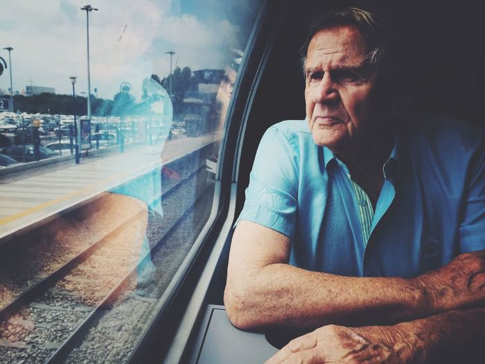 Senior Man Looking Out Through Train Window