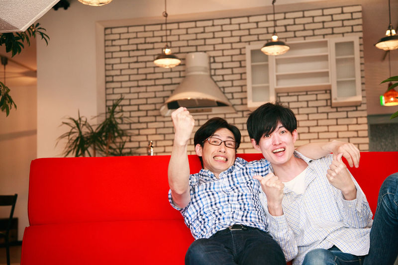 Portrait of happy friends gesturing while sitting on sofa at home
