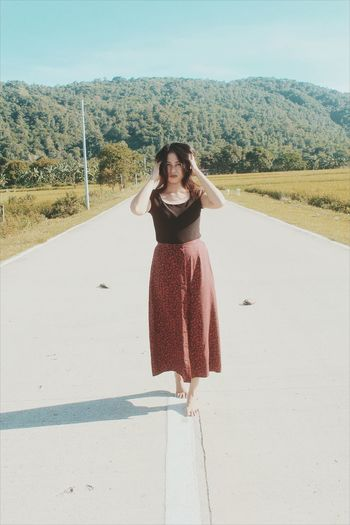 Portrait Of Young Woman Standing On Road During Sunny Day
