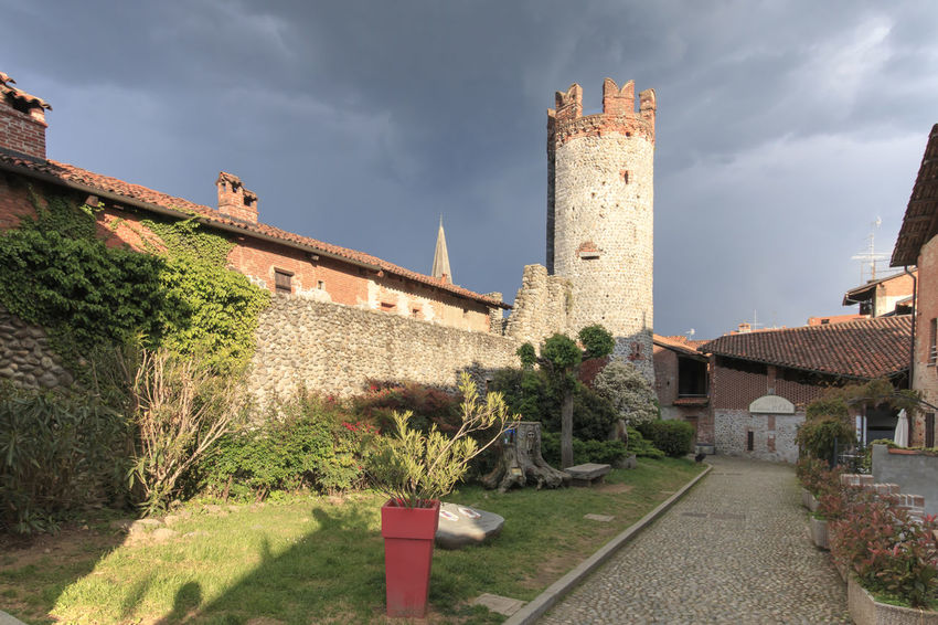 Candelo, Biella - May 4, 2016: View form the outside of the Medieval village of Ricetto di Candelo in Piedmont, used as a refuge in times of attack during the Middle Age. Architectural Column Architecture Biella Building Exterior Built Structure Candelo Candelo In Fiore Cloud Cloud - Sky Cloudy Day Diminishing Perspective Grass Growth Historic Italy Medieval Village Nature No People Outdoors Plant Ricetto Di Candelo  Sky The Way Forward Walkway