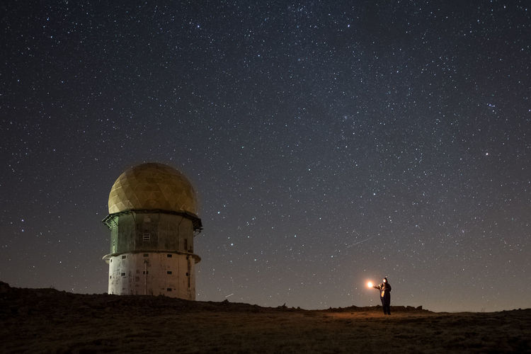 Young woman standing by lighthouse on field against star field at night