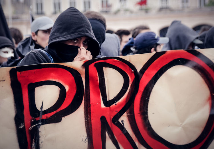 Anarchy Protest Clothing Communication Crowd Day Demonstration Emotion Focus On Foreground Group Of People Incidental People Leisure Activity Lifestyles Men Message Outdoors People Protesting Protestor Real People Rear View Riot Streamer Text Warm Clothing Springtime Decadence