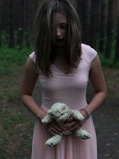 Young woman holding teddy bear while standing in forest