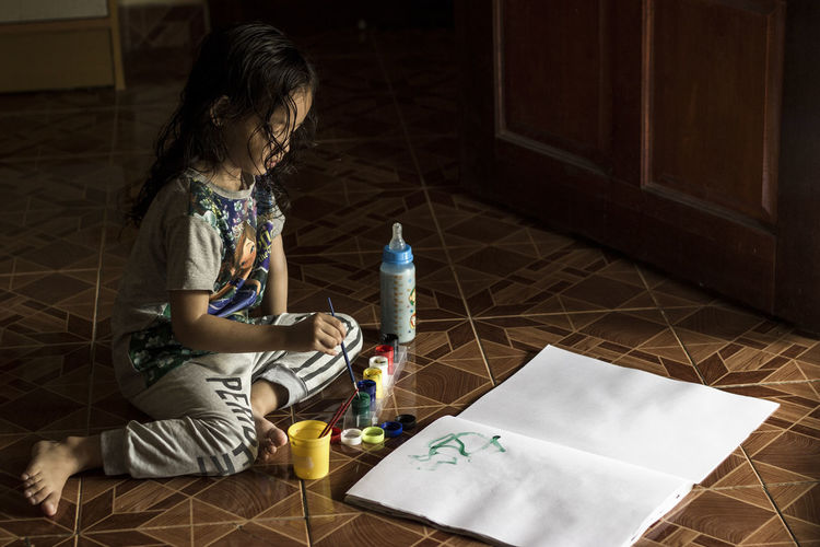 Full length of girl painting in paper while sitting on floor at home