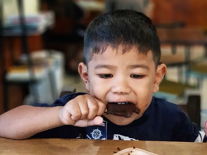 Close-up of boy eating food on table