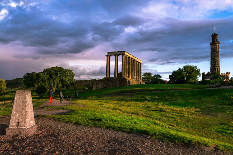 """Calton Hill is one of Edinburgh's main hills, set right in the city centre. It is unmistakable with its Athenian acropolis poking above the skyline. The acropolis is in fact an unfinished monument - originally called the """"National Monument"""". Initiated in 1816, a year after Napoleon's defeat at Waterloo, it was meant to be a replica of the Parthenon in Athens, as a memorial to those who had died in the Napoleonic Wars. Building began in 1822, but funds ran dry and celebrated Edinburgh architect William Playfair only saw a facade of his building completed. It was dubbed """"Edinburgh's shame"""", but it's now a popular landmark and it's a lot of fun crawling up and down its giant steps. Plans since to complete the building never really get much support. Calton Hill Edinburgh National Monument Architecture Building Exterior Built Structure Cloud - Sky Day Grass History Memorial Nature No People Outdoors Sky Travel Destinations Tree"""