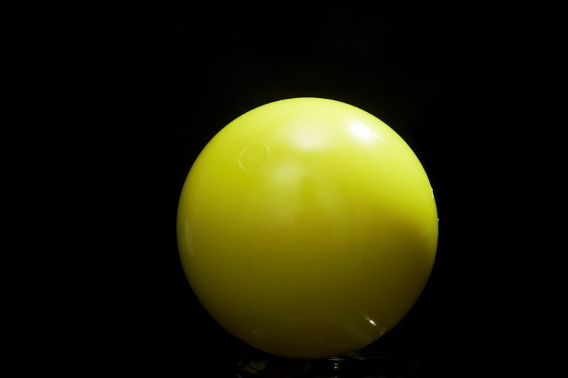 Close-up of yellow balloons against black background