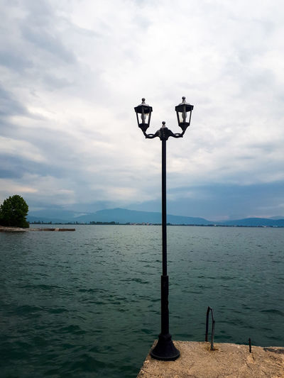 Street light on wooden post by sea against sky