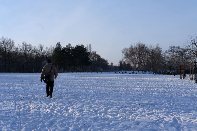 Rear view of man walking on snow covered field