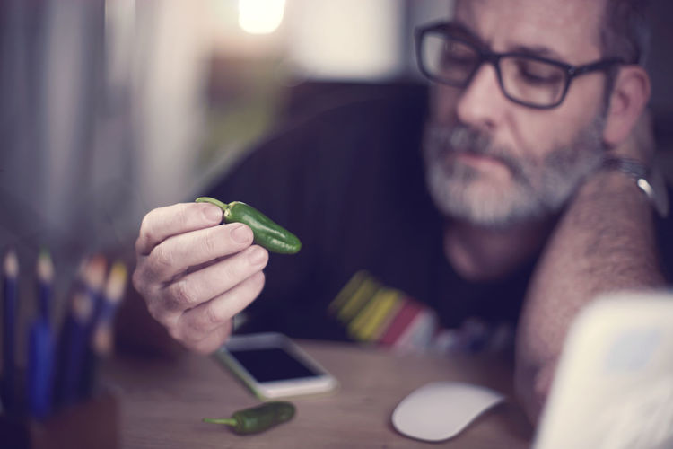 Thoughtful man holding green chili pepper at desk in workshop