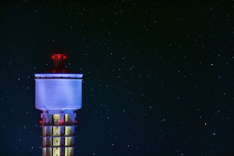 Illuminated water tank against star field at night