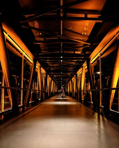 Woman Fashion Orange Color Illuminated Bridge - Man Made Structure City Architecture Built Structure Covered Bridge vanishing point The Way Forward Pathway Diminishing Perspective Straight Elevated Walkway Passageway