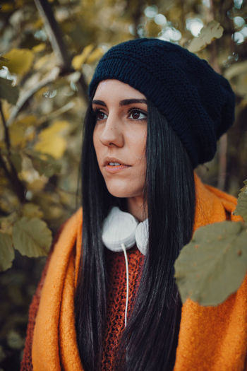 Close-up of woman wearing knit hat standing in forest
