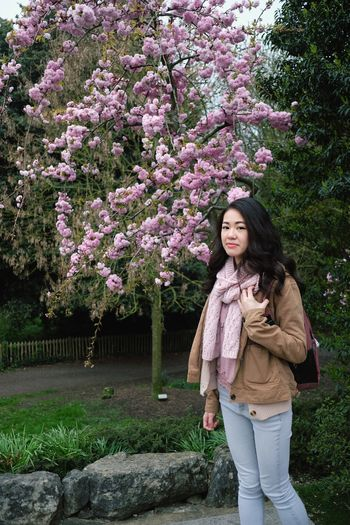 Full length of smiling woman standing by flower tree