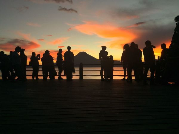 The stunning backdrop of the majestic volcanoes, the serene water, the lively Mayan culture and the perfect sunset...This is the peaceful life in Lake Atitlan. Sunset Real People Sky Silhouette Lifestyles Men Women Leisure Activity Standing Water Nature Sea Outdoors Cloud - Sky Beauty In Nature Scenics Friendship Togetherness Day Atitlan Lake Guatemala Volcano Miles Away