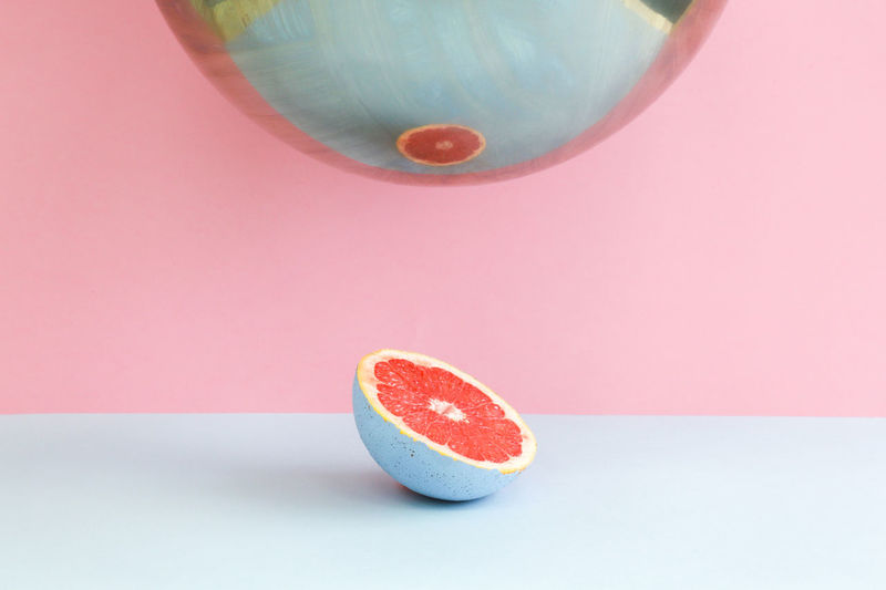 Close-up of citrus grapefruit slice reflecting on mirror