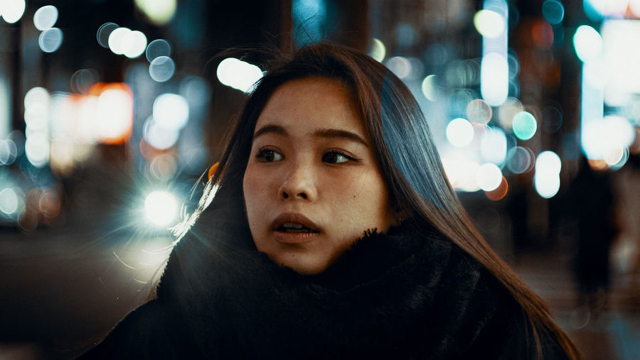 Portrait of young woman in illuminated city at night