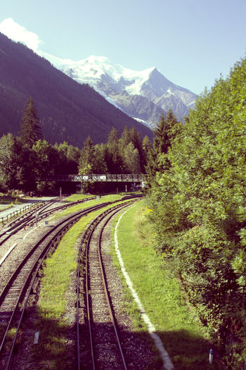 Railroad tracks amidst trees and mountains against sky