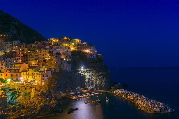 Illuminated city by sea against clear blue sky at dusk