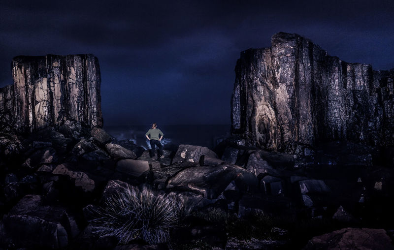 Rear view of woman sitting on rock at beach against sky at night