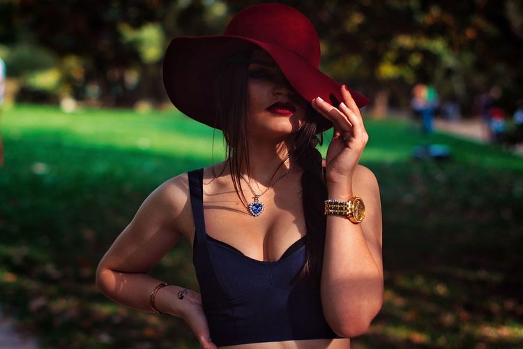Portrait Of Sensuous Woman Wearing Red Hat In Park