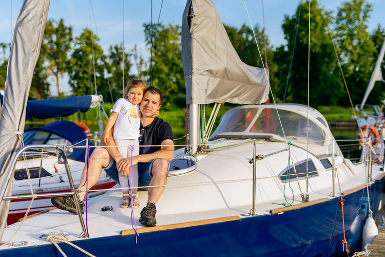 Portrait of girl with father sitting on yacht