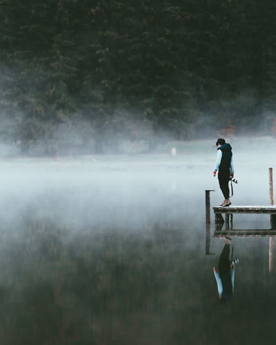 Man Standing On Pier Over Lake In Forest EyeEm Best Shots Hat Man Pier Reflection Standing Day Fog Full Length Lake Leisure Activity Lifestyles Men Nature One Person Outdoors Outdoors Photograpghy  People Real People Side View Sky Standing Standing Water Water Young Adult