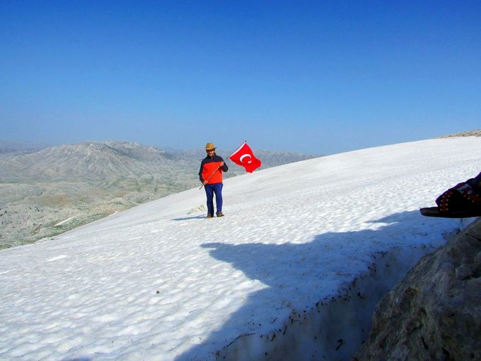 Full length of man holding turkish flag on snow covered land against sky