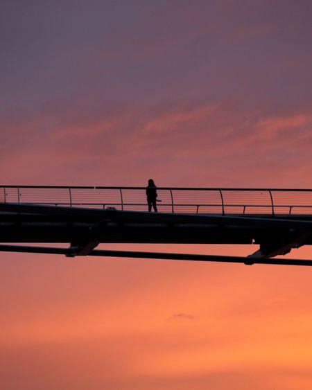 Silhouette man on bridge against sky during sunset