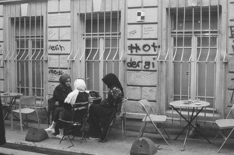 A group of girls sit and chat outside of a cafe in Istanbul, Turkey. - Photos taken on 35mm film with Canon AE-1 Program analog camera. Streetwise Photography Streetphotography Street Analogue Photography Analog 35mm Film Film Photography Canon AE-1 Canon Canon AE-1 Program  Black And White Blackandwhite Black & White The Week on EyeEm Best Of EyeEm My Best Photo Fomapan Fomapan400 Leisure Activity Communication Group Of People The Art Of Street Photography