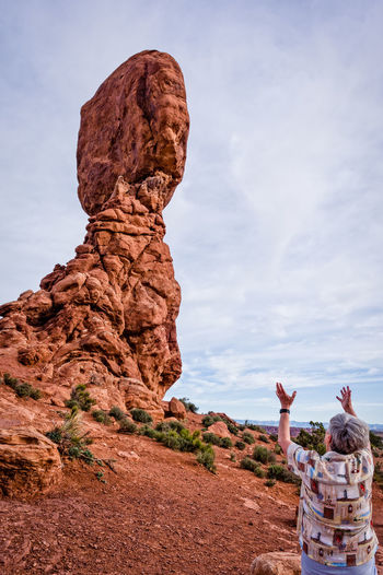 Senior woman gesturing against rock formation against sky