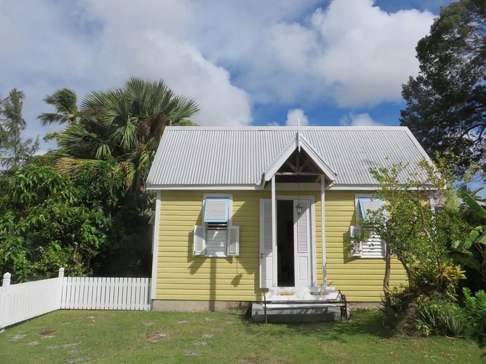 Traditional chattel house in Barbados Architecture Building Exterior Built Structure Chattel House Cloud - Sky Door Grass House No People Outdoors Residential Structure Sky Traditional Tree Yellow
