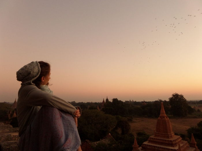 Woman looking at historic temples against sky during sunrise