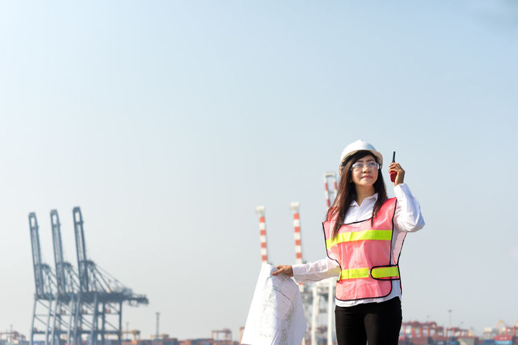 Female architect with blueprint standing against clear sky at construction site