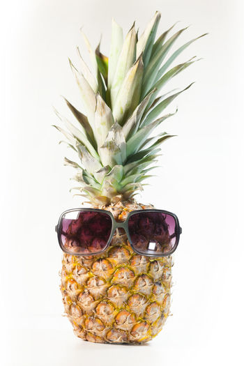 Pineapple Tropical Fruit Studio Shot Close-up Indoors  White Background Sunglasses Healthy Eating Food Fruit Wellbeing Yellow Freshness Vertical Refreshment Ripe Juicy Diet Season  Funny Object Unusual Summer Stylish Party Creative Mood Holiday Accessories Isolated Vibes Travel Fun Overhead Cool Sunlight Vacation Cheerful Happy Design Sunny Heat Sweet Symbol Organic Face Sunshine Cute